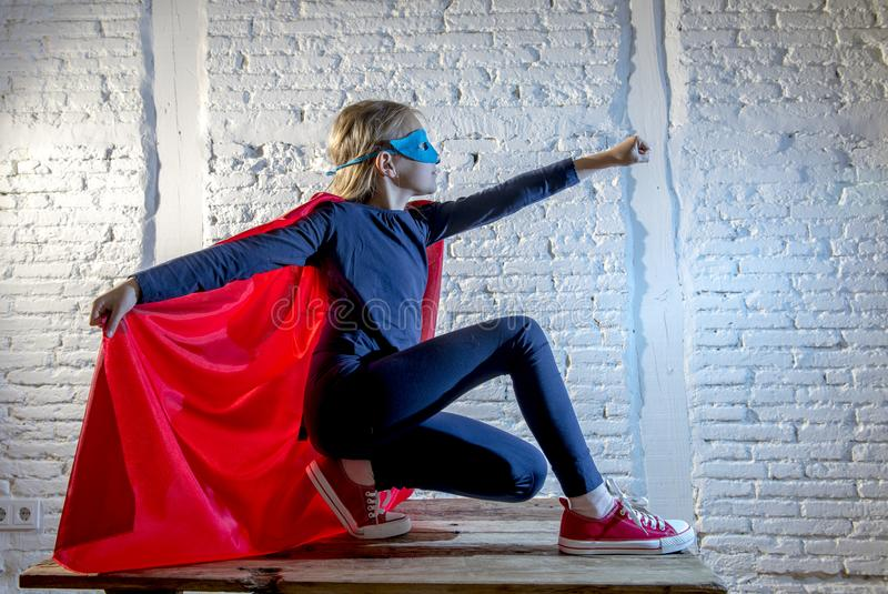 Female child 7 or 8 years old young girl performing happy and excited posing wearing cap and mask in super hero fantasy costume lo. Oking playful in studio stock photography