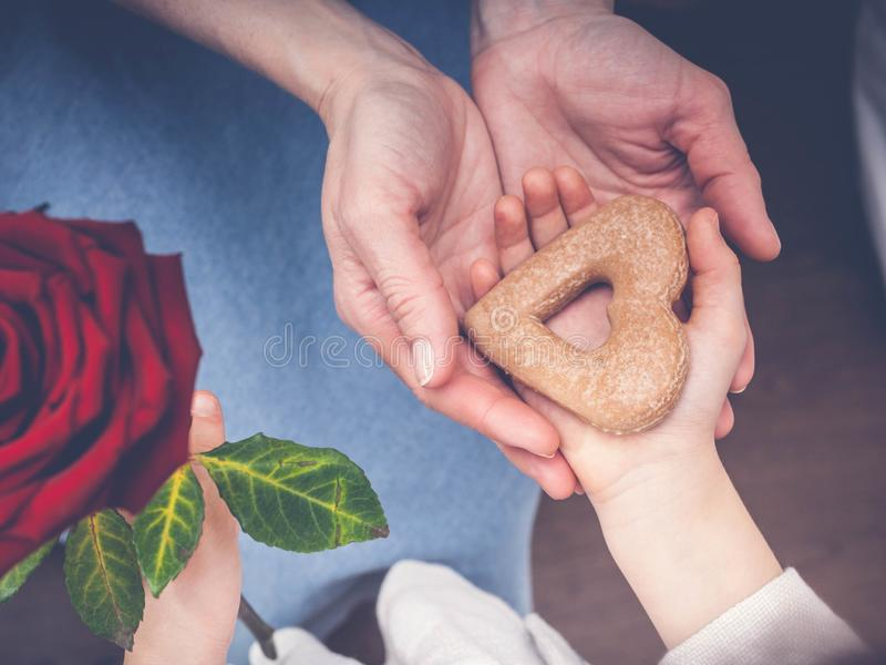 Female and children`s hands hold cookies in the form of heart. Concept by the Mother`s Day. Vintage toning royalty free stock photography