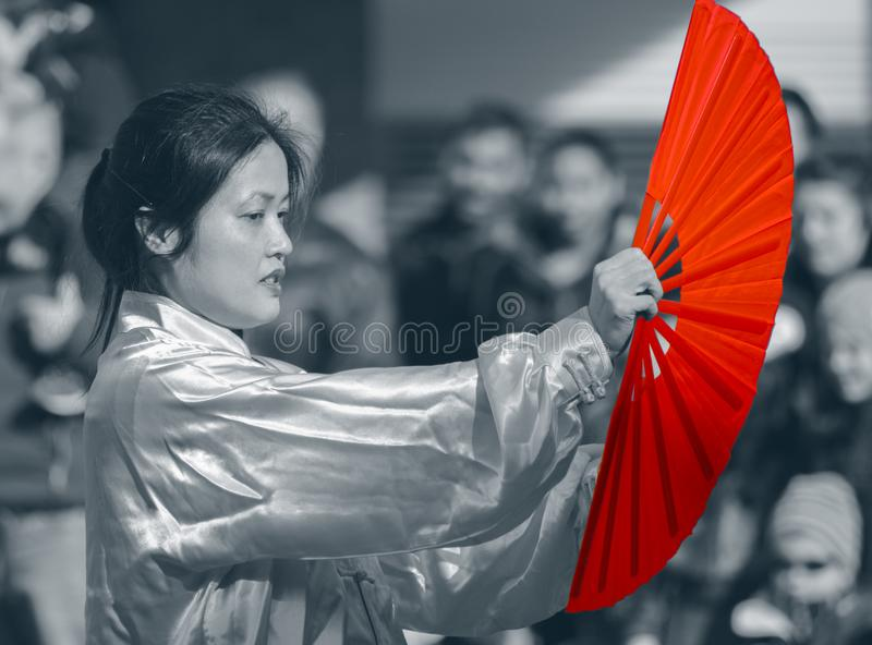 Female Chinese woman with Red fan. A young Chinese woman performing a beautiful fan dance at the Chinese New Year celebrations in Woking UK year of the sheep royalty free stock images