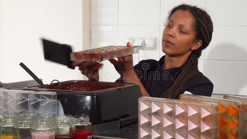 Female chocolatier working at her kitchen. Beautiful African American female chocolatier working at her kitchen preparing handmade delicious candy. Professional stock photo