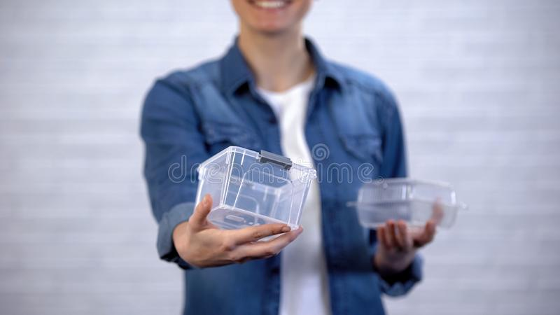 Female choosing bioplastic food container instead non-disposable box, pollution. Stock photo stock image