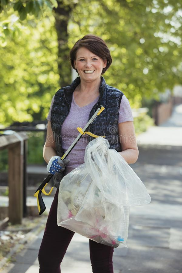 Female City Cleaner Portrait. A portrait of a mature woman standing in a park, participating in a city clean up royalty free stock images