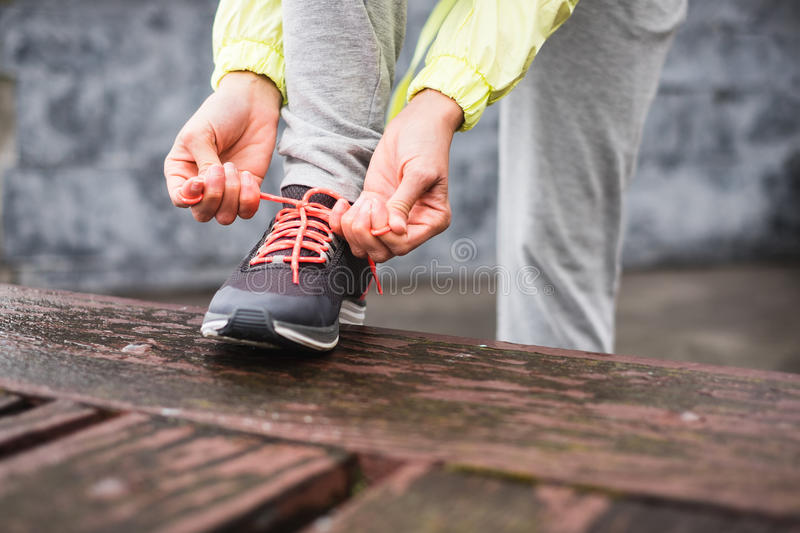 Female city runner lacing sport footwear. Female runner tying sport shoes laces before running urban challenge. Sporty unrecognizable woman lacing footwear stock photography