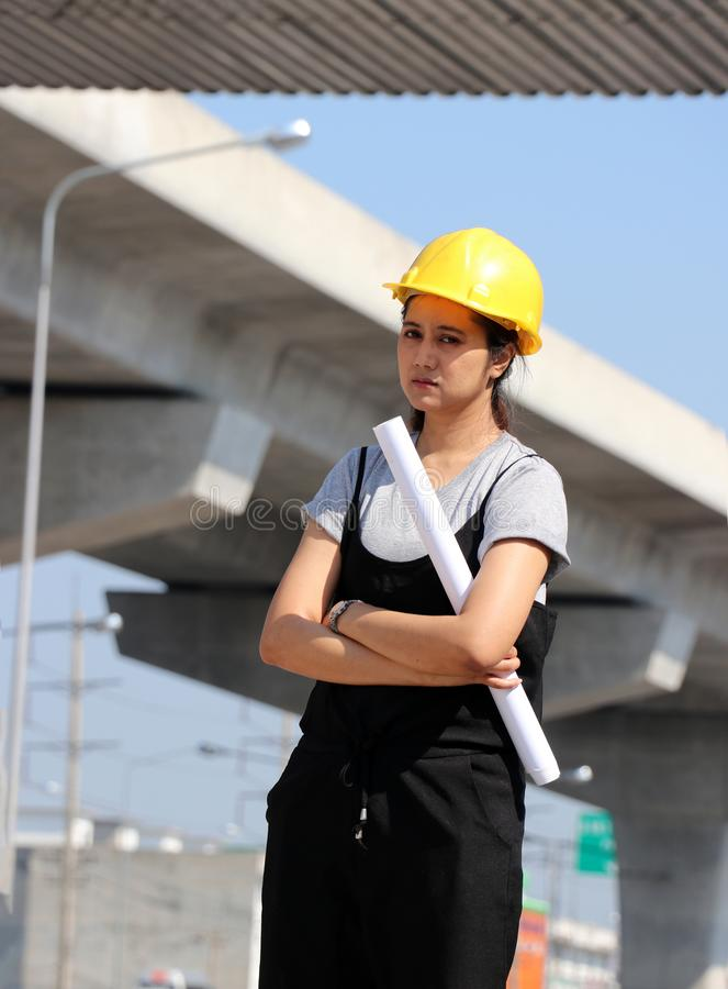 Female civil engineer or architect with yellow helmet, standing and hugging chest with project drafts while. In the work area stock photo