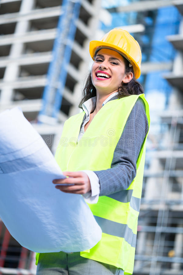 Female civil engineer studying drafts visiting construction site royalty free stock image