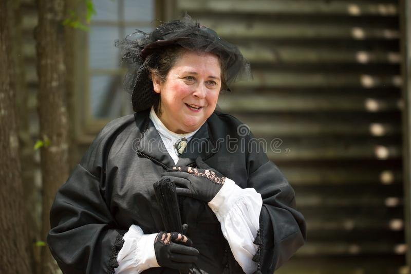 Female Civil War Reenactor. HUNTERSVILLE, NC - JUNE 1, 2019 USA:  A woman in antebellum mourning clothes interacts with visitors at an American Civil War battle royalty free stock photos