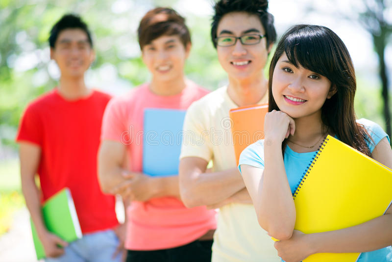 Female classmate. Portrait of a pretty student with her male classmates standing behind royalty free stock image