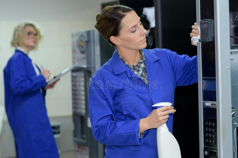 Female cleaner cleaning vending machine stock images