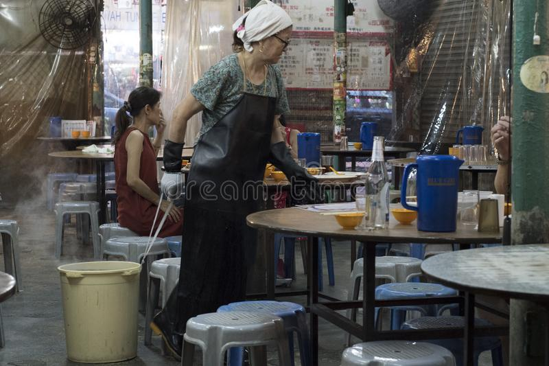 Female cleaner cleans the tables at a restaurant in Hong Kong. royalty free stock photo