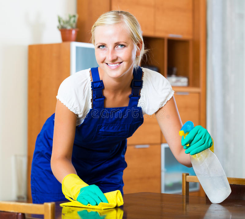 Female cleaner doing regular clean-up. Professional young female cleaner doing regular clean-up in home interior stock photography