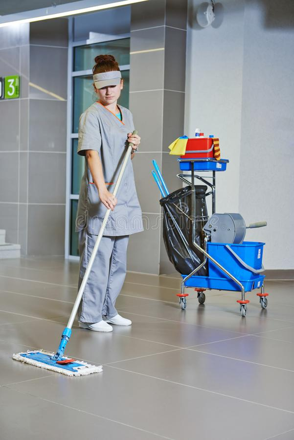 Cleaning services. Woman clean the floor with mop. Female cleaner with mop and uniform cleaning hall floor of public business building stock images
