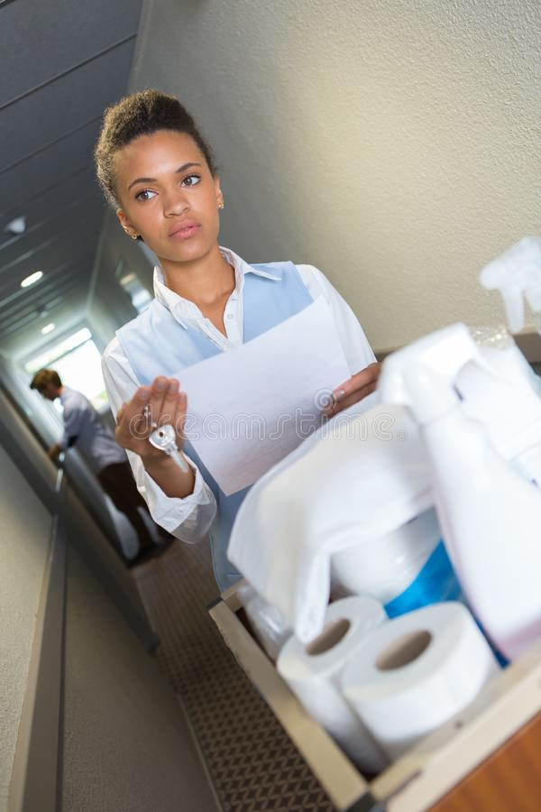 Female cleaner in uniform with mop and cleaning equipment royalty free stock photo
