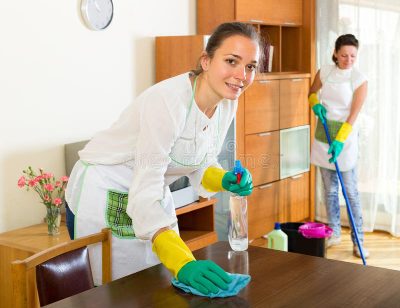Female cleaners cleaning room stock photo