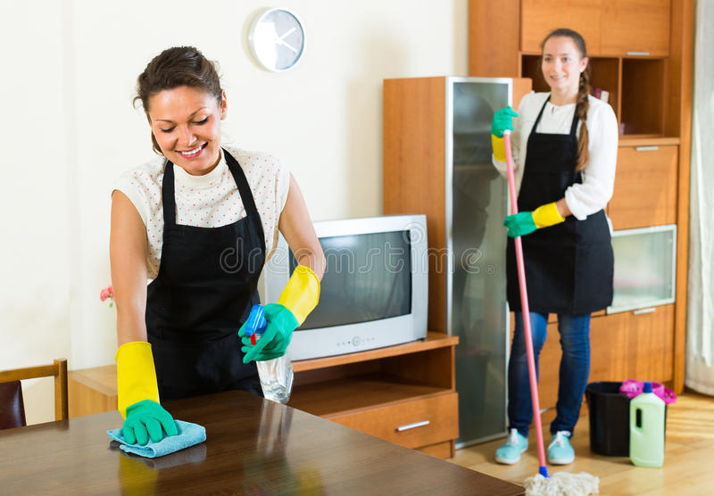 Female cleaners cleaning room stock image