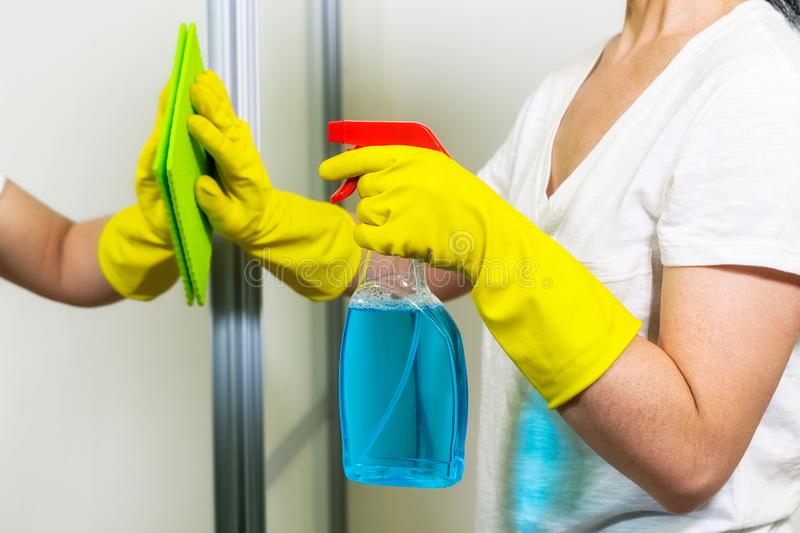 Female cleaning mirror with cleaning agents. Close up royalty free stock photography