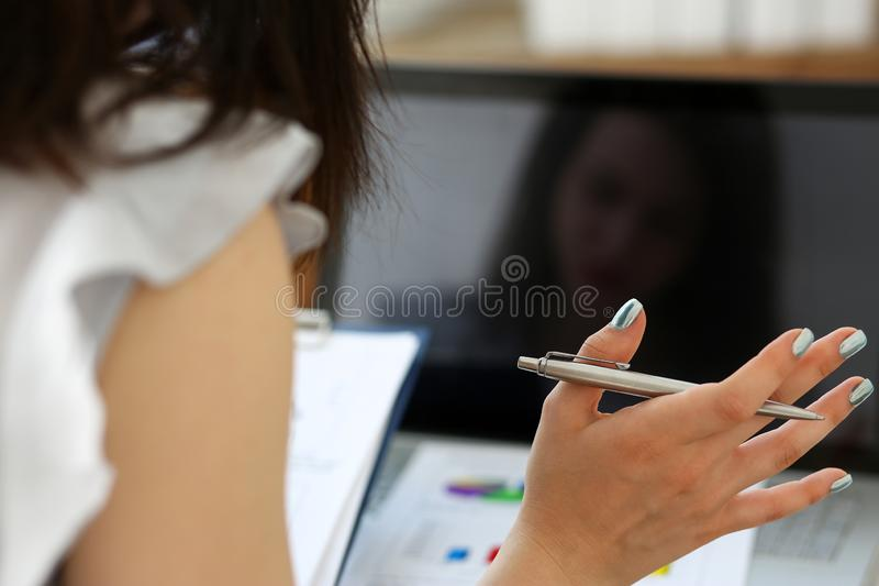 Female clerk hand holding silver pen and work with some important documents on computer royalty free stock images