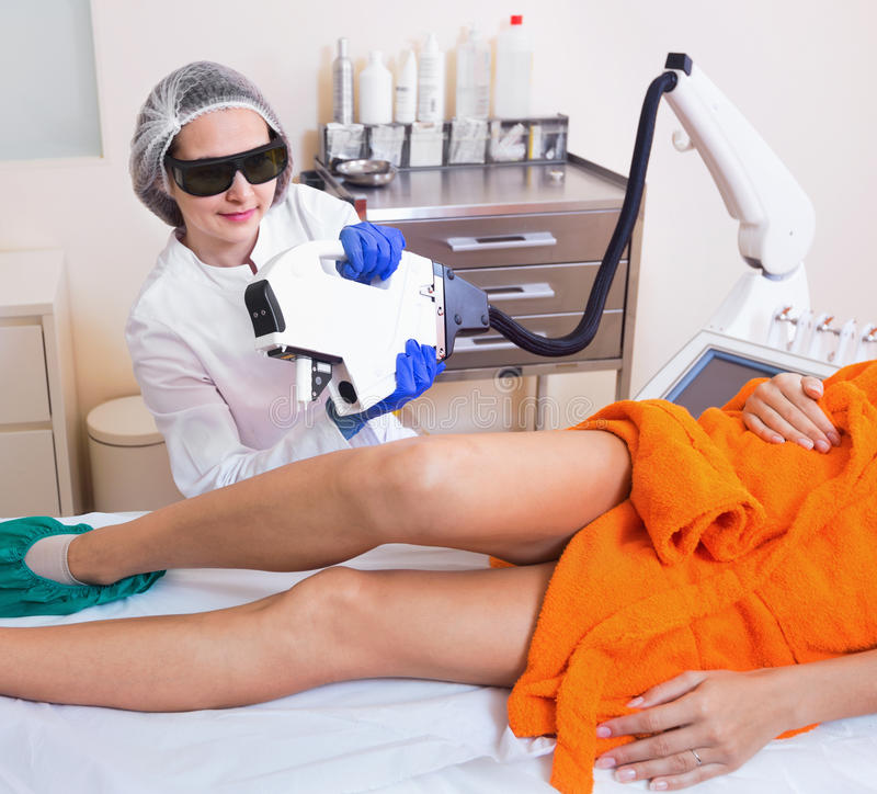 Female client doing laser hair removal from legs. Diligent friendly female client doing laser hair removal from legs stock photo