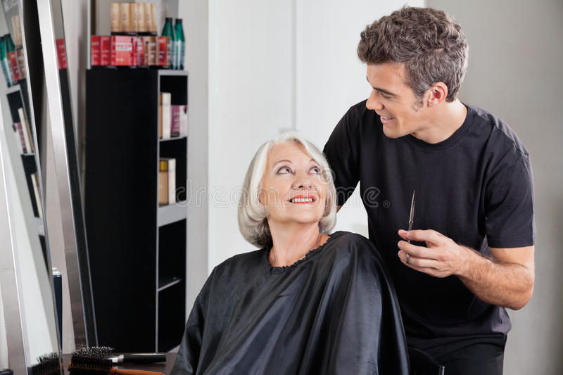 Female Client And Hairdresser Looking At Each. Happy female client and hairdresser looking at each other in beauty salon royalty free stock image