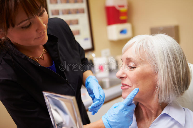 Female Client Looking In Mirror After Botox Treatment. Looking Happy stock images