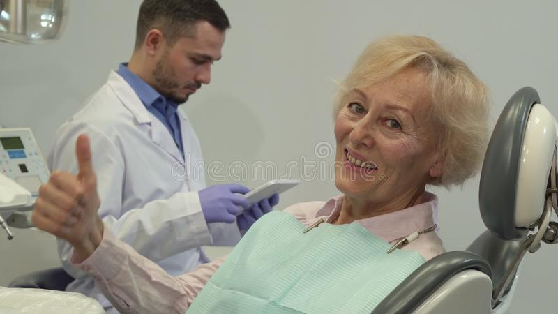 Female client shows her thumb up on the dental chair stock image