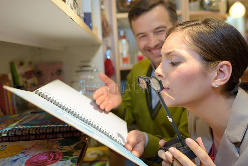Female client trying magnifying glasses at retail store stock photos