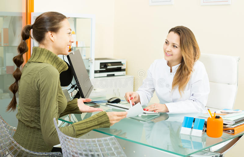 Female client visiting in aesthetic medicine center. Young female client visiting consultation in aesthetic medicine center. Focus on doctor royalty free stock photos