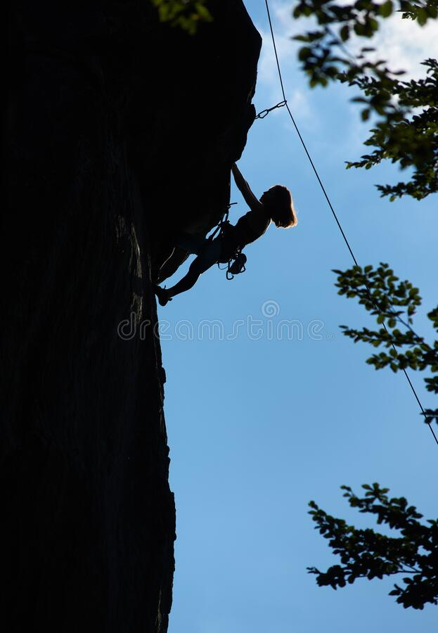 Female climber ascending mountain at night. royalty free stock photography