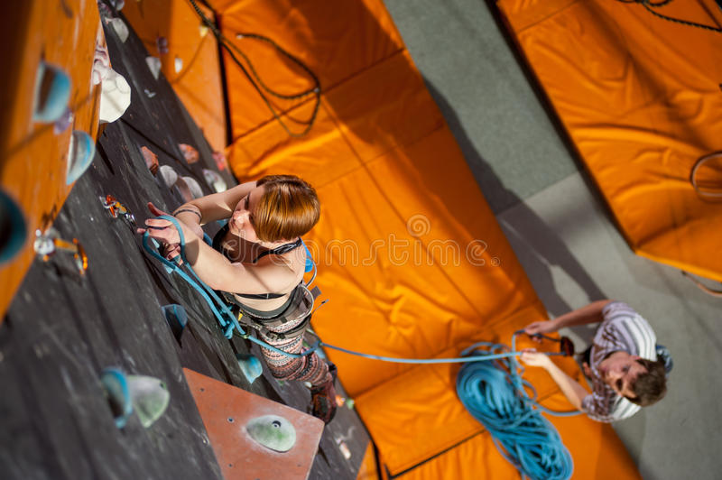 Female climber is climbing up on indoor rock-climbing wall. Muscular female is climbing up with carbines and rope on an indoor rock-climbing wall. Man standing stock photos