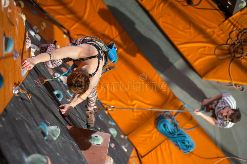 Female climber is climbing up on indoor rock-climbing wall. Strong young women is climbing up with carbines and rope on an indoor rock-climbing wall. Man stock photography
