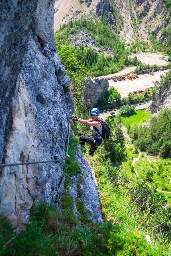 Female climber hanging from a via ferrata cable on Astragalus route, a popular tourist attraction in Bicaz Gorge/Cheile Bicazului stock photography