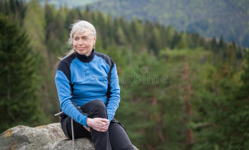 Female climber on the peak of rock with climbing equipment. Close-up portrait of woman in a blue jacket sit and relax on the peak of rock and watching away on royalty free stock image
