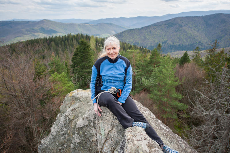 Female climber on the peak of rock with climbing equipment. Smiling woman in a blue jacket sit and relax on the peak of rock and watching to the camera, on royalty free stock photos