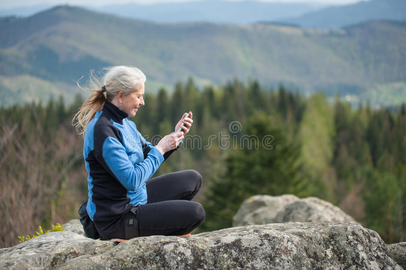 Female climber on the top of rock. Woman in a blue jacket sitting on the rock cliff and holding a mobile phone on the blurred greenery background. Connected royalty free stock image