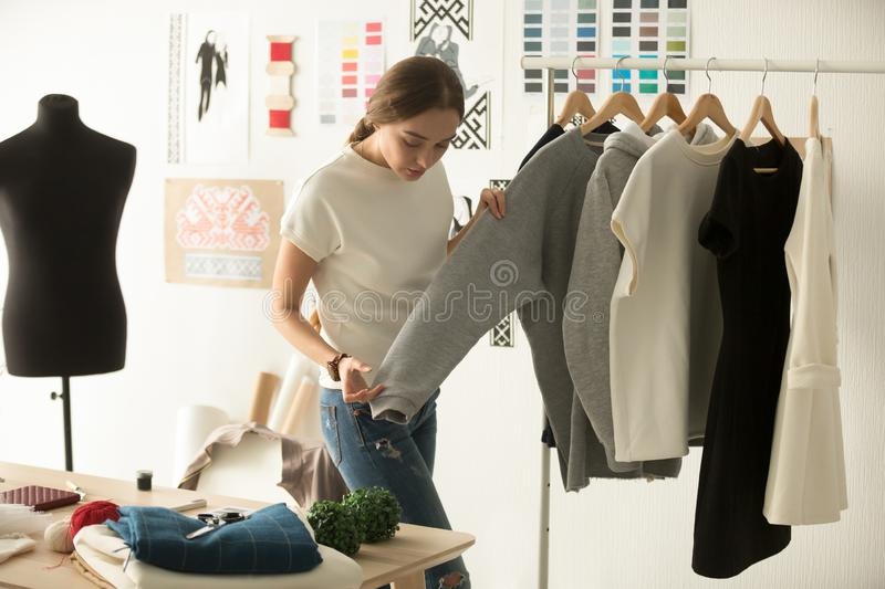 Female clothes designer working with new woman wear in workshop royalty free stock images