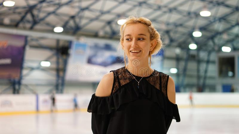 Female coach in figure skating at indoor rink. Female coach in figure skating in black dress at indoor rink stock photography