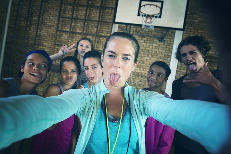 Female coach and high school kids taking a selfie stock image