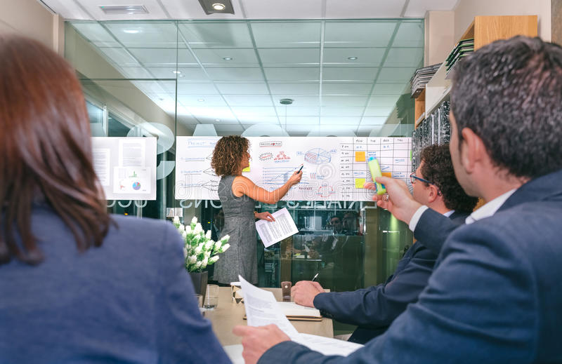 Female coach looking business graph while businessman having question royalty free stock photos