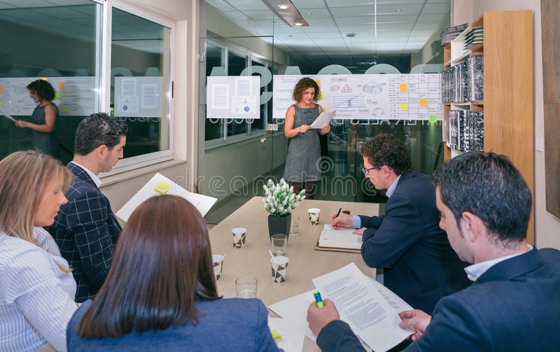 Female coach looking project management in business team training. Female coach talking while looking project management to business team sitting at table in royalty free stock photos