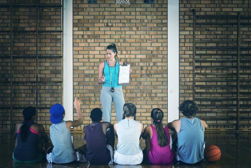 Female coach mentoring high school kids stock photography
