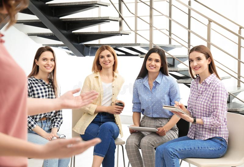 Female coach working with ladies in room. Women power concept stock photos