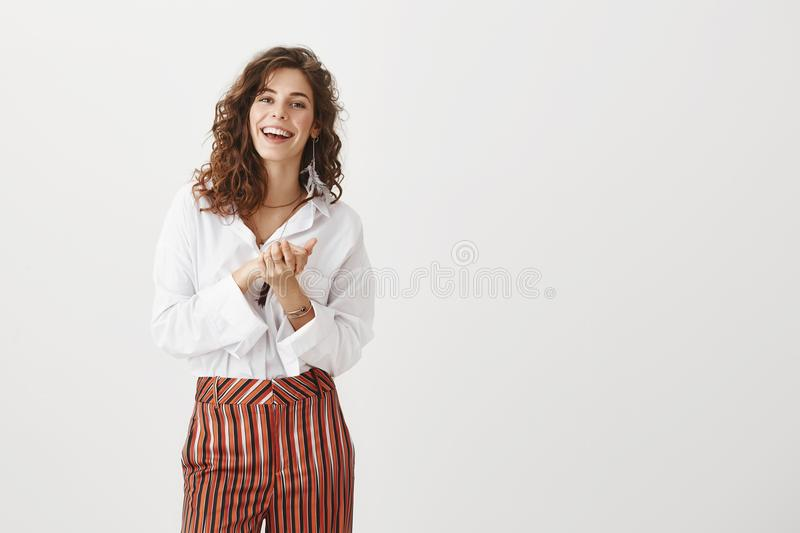 Female colleague clapping hands, applauding friend who achieved success. Portrait of happy carefree woman with curly. Hair in fashionable clothes, holding palms stock photo