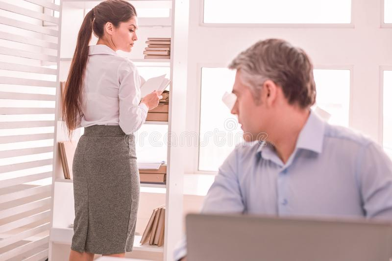 Gray-haired man looking at his colleague dress stock photo