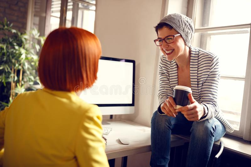 Female colleagues chat in office royalty free stock photos