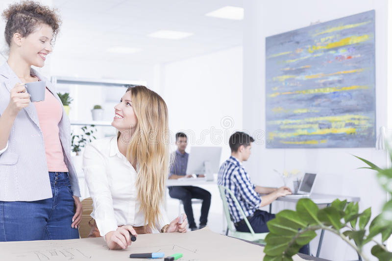 Female colleagues talking in office stock photo