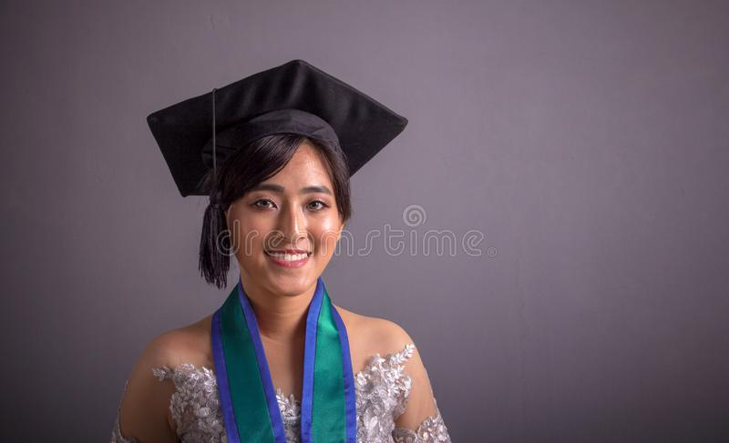 Female college student in graduation hat closeup portrait over grey. Young attractive Asian female college student in graduation hat and traditional dress stock photography