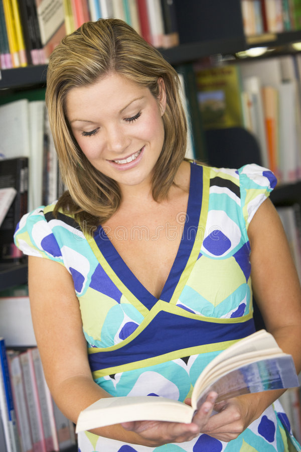 Female College Student Reading In A Library Royalty Free Stock Images