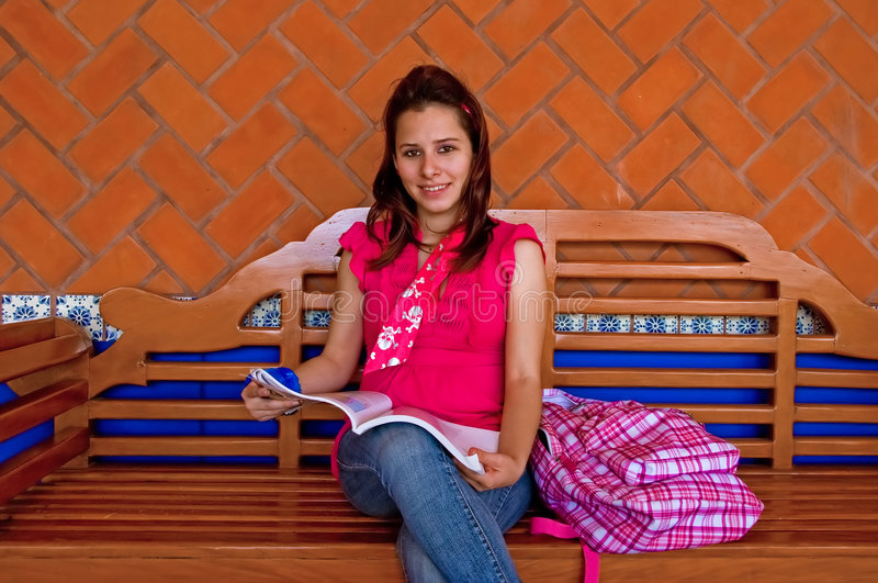 Female college student reading on long bench royalty free stock photos