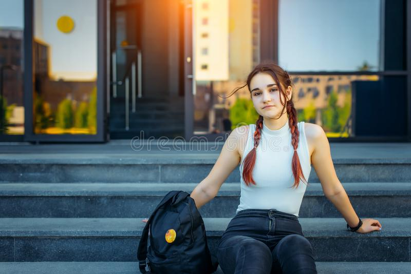 Female college student sitting on stairs with backpack, close up. Young attractive girl in while studying at university campus stock photo