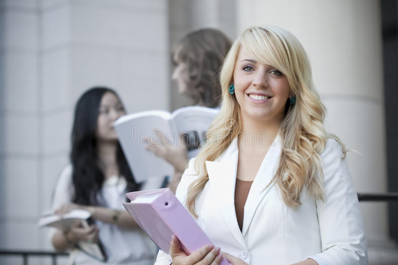 Female College Student Smiling. An attractive female college student walks out of a classroom building on campus with two of her classmates in the background royalty free stock photography