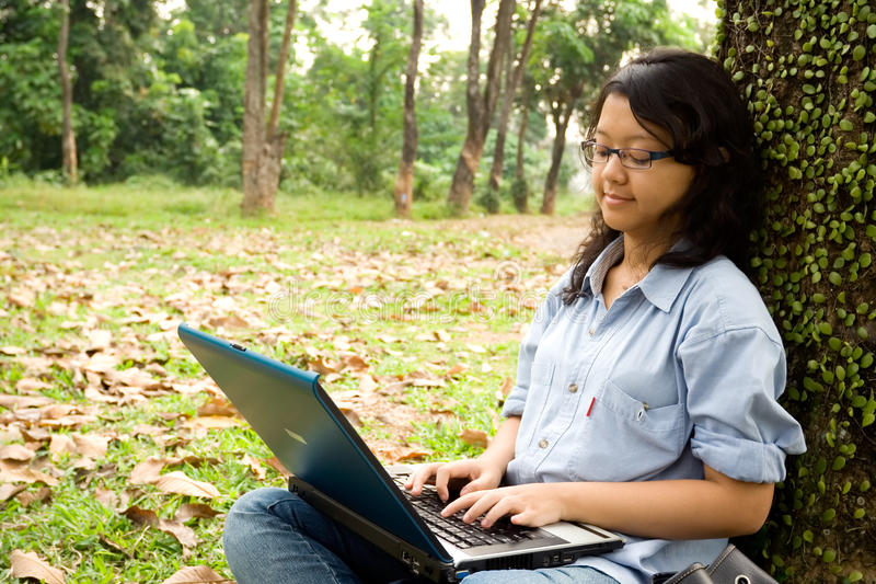 Female college student working on a laptop stock images